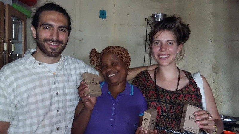 Members of Lumkani founding team with a recipient of the early-warning fire detection system